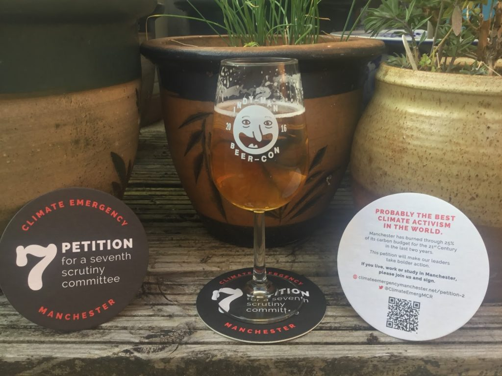 Two of CEM's petition beermats sit either side of a glass of beer